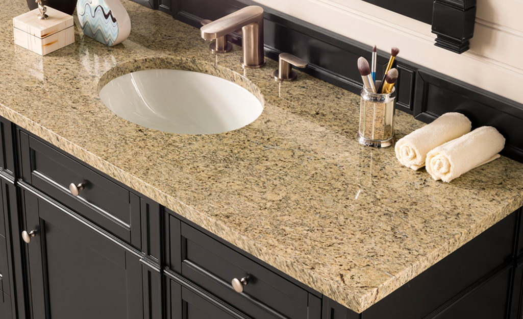 A beige colored granite bathroom countertop.