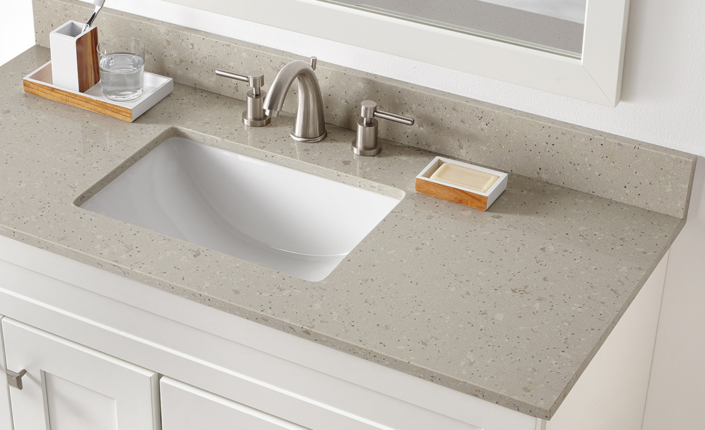 A bathroom vanity countertop made of engineered quartz.