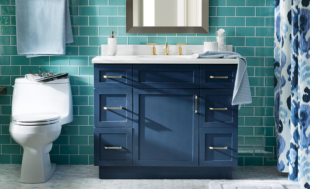 A coastal inspired bathroom with a blue vanity.