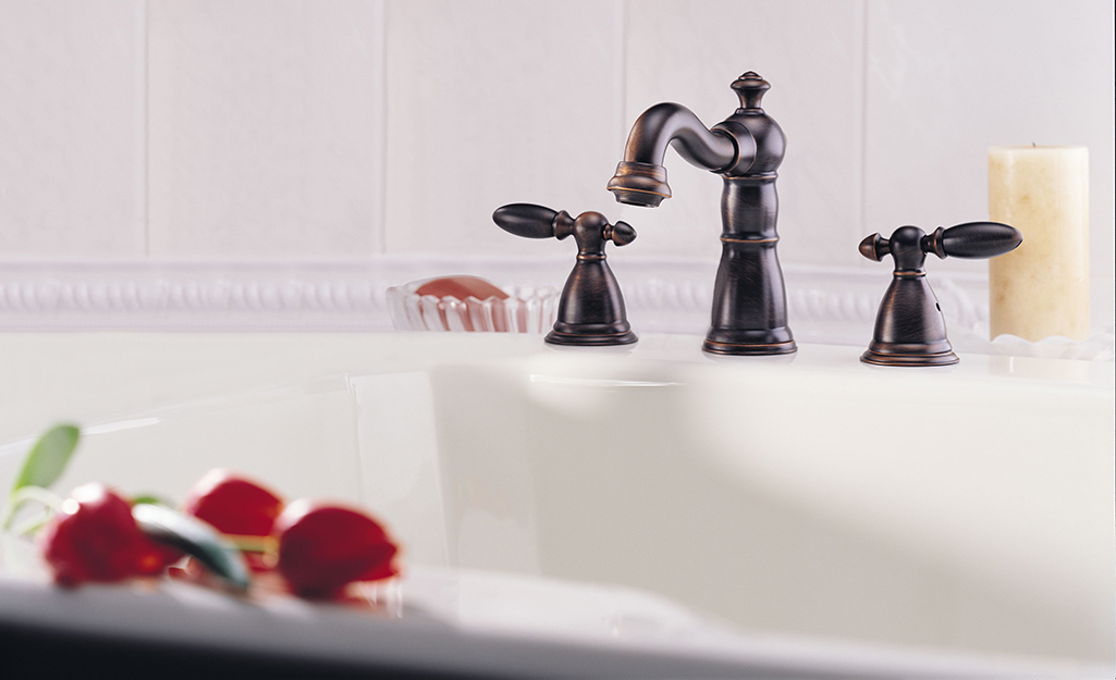 A tub faucet with a dark finish on a white porcelain tub.