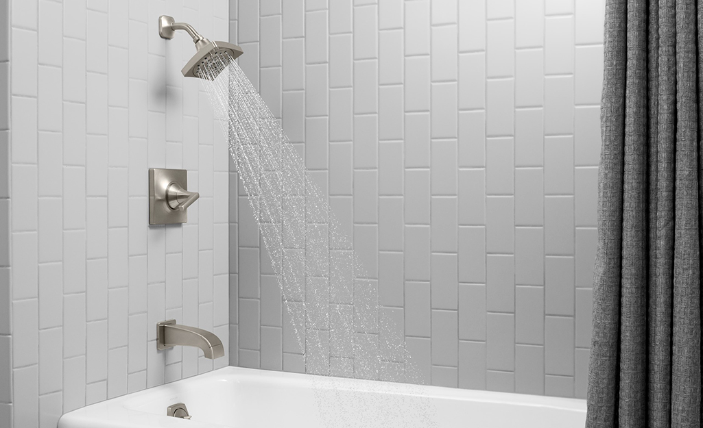 A  wall-mounted shower head and faucet.