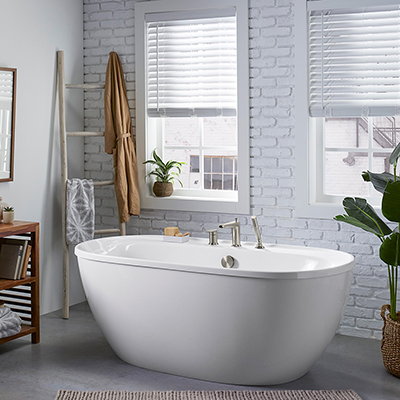 A white freestanding bathtub in a bathroom with subway tiles.