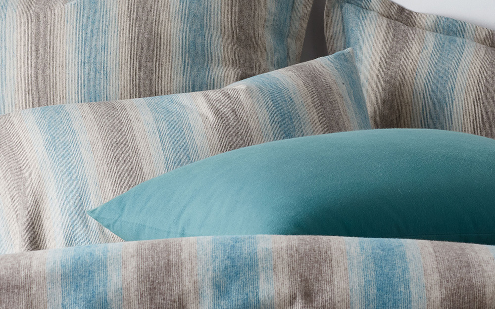 Blue and brown striped pillows piled on a bed.