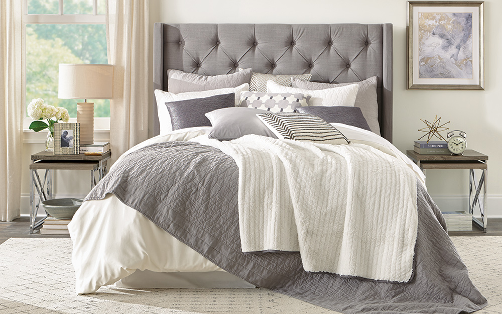 A bed made of grey and white bedding.