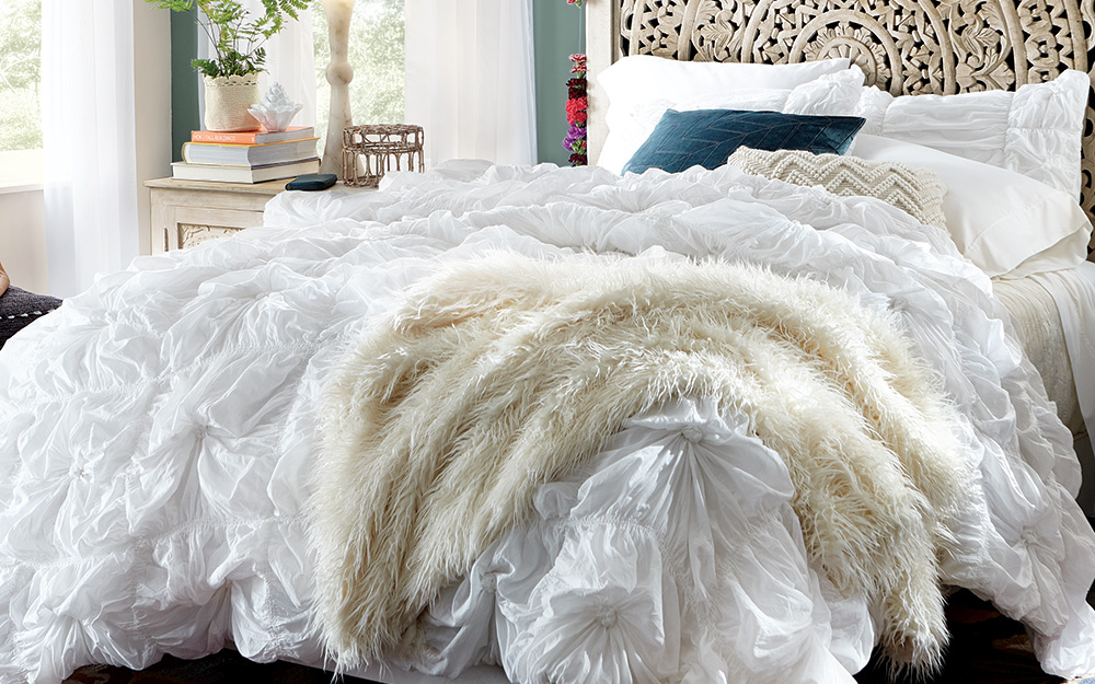 A bed made with delicate blankets.