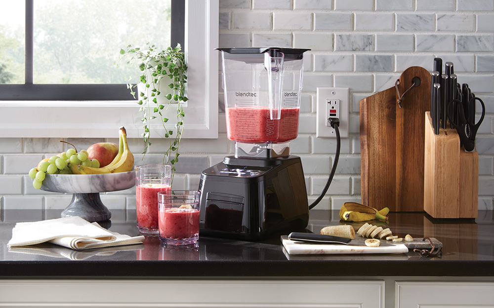 A countertop blender and two glasses filled with strawberry and banana smoothies.