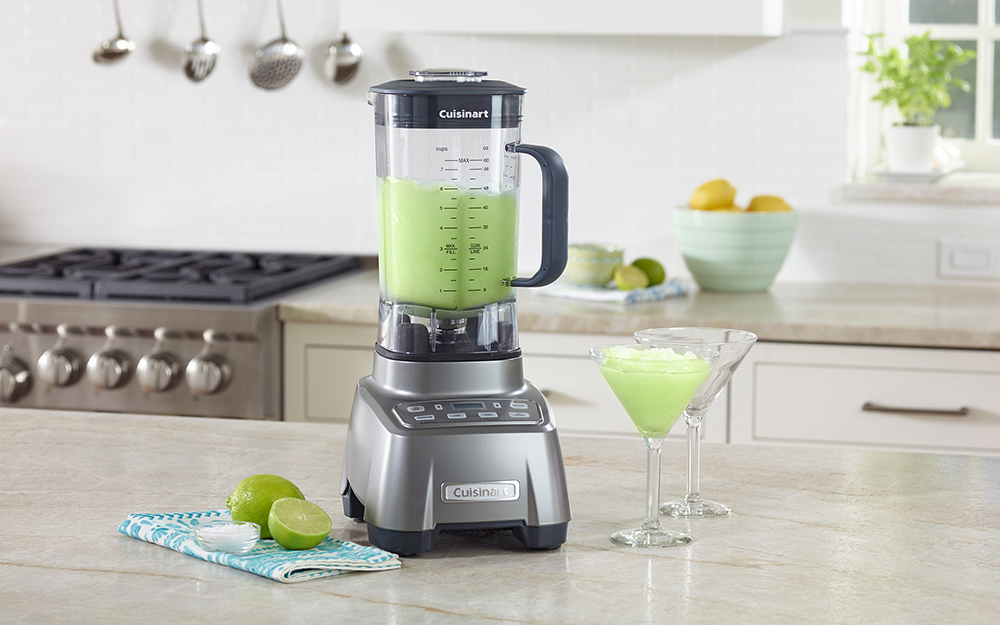 A countertop blender and a glass filled with margarita mix, sitting on a counter beside some limes.