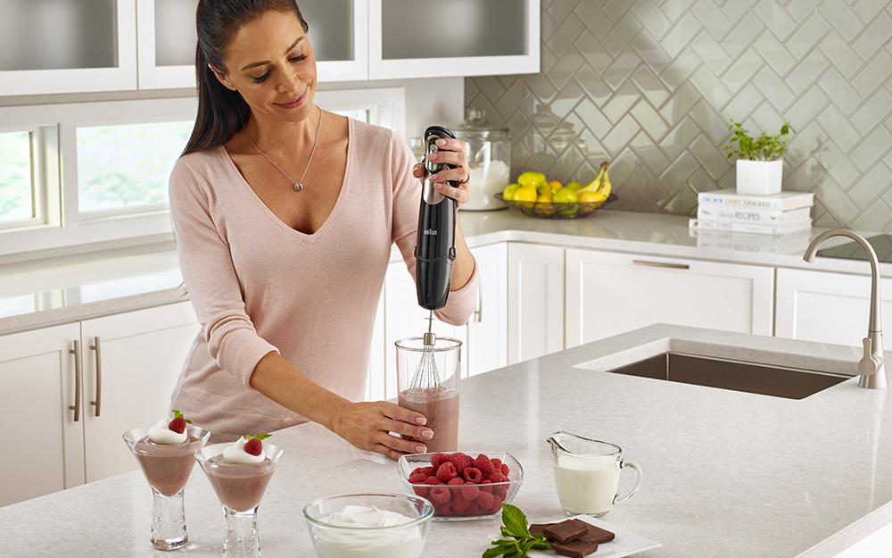 Woman using a handheld blender to combine chocolate, milk and raspberries for cream-topped desserts.