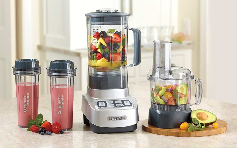 A combination blender and food processor filled with fruits.