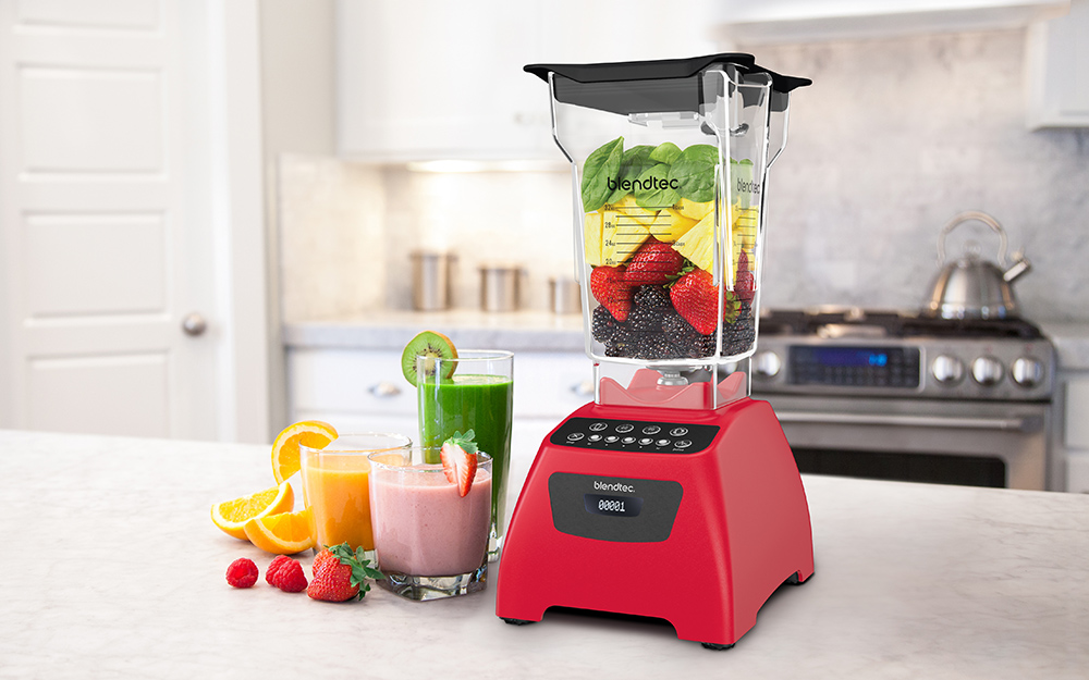 Larger countertop blender and three glasses filled with blended drinks.
