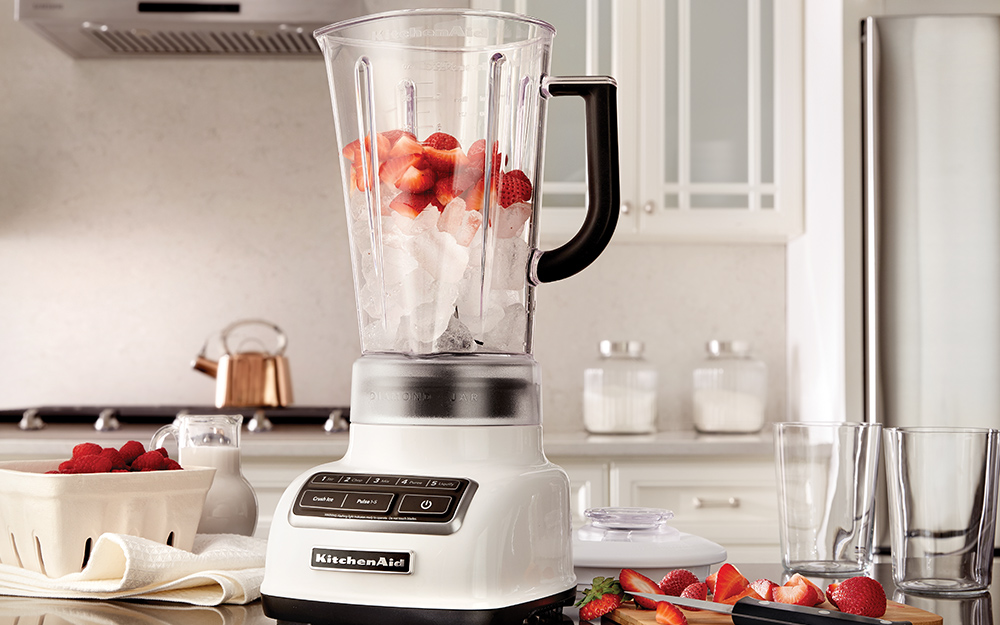 A countertop blender filled with ice cubes and topped off with strawberries.