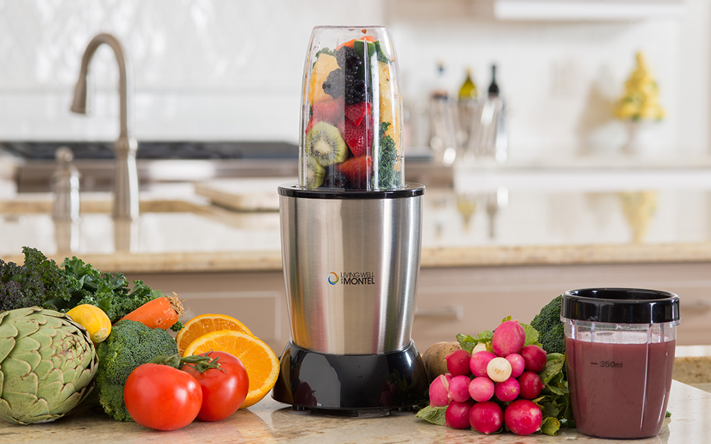 A single serving blender, fruits and vegetables and a travel cup on a counter.