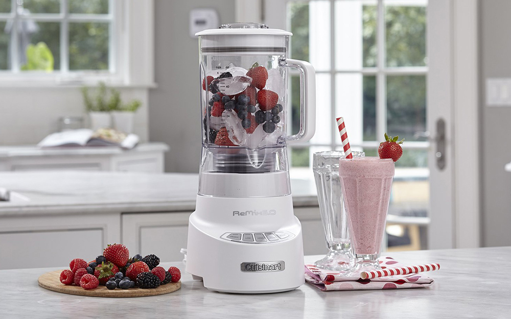 A small blender sitting on a countertop beside a strawberry milkshake and a plate of berries.