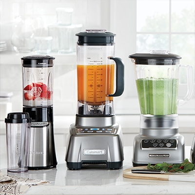 Three different kinds on blenders, filled in the company of different foods, sitting supported by a counter.