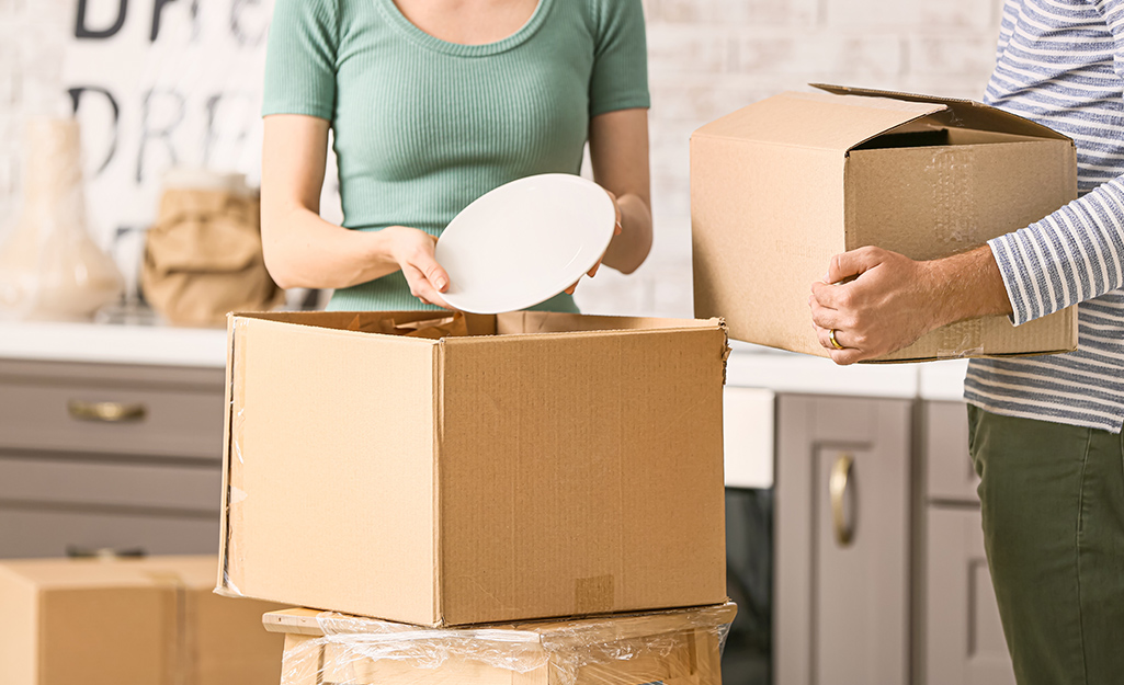 Two women pack dishes into cardboard moving boxes.