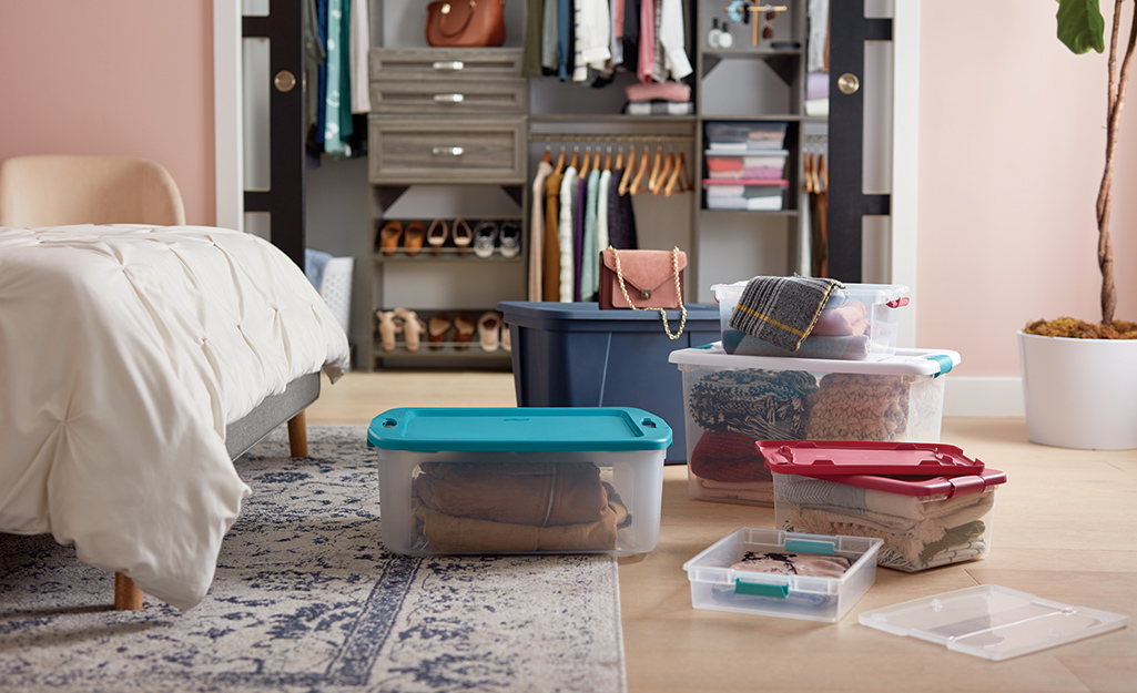 Plastic moving bins and storage totes are used to pack a bedroom closet.