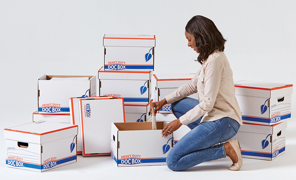 A woman uses specialty file boxes to sort documents.