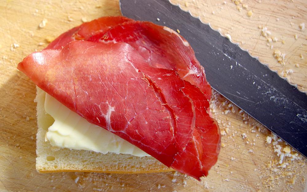 A serrate knife next to an open faced sandwich.