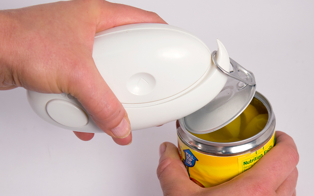 Someone using a handheld can opener to open a can.