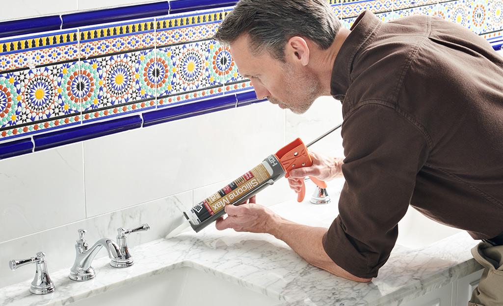 Một người đàn ông sử dụng súng caulk để niêm phong quầy trong phòng tắm.