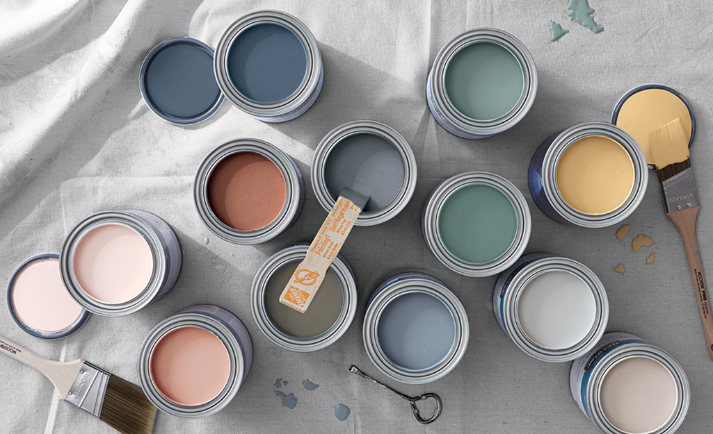 Open paint cans on a drop cloth display various paint colors.