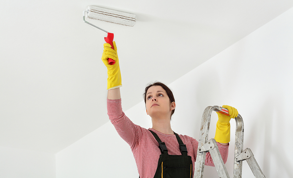 A woman on a ladder uses a paint roller to paint a ceiling.