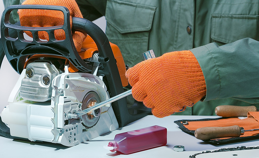 A person maintaining a chainsaw.
