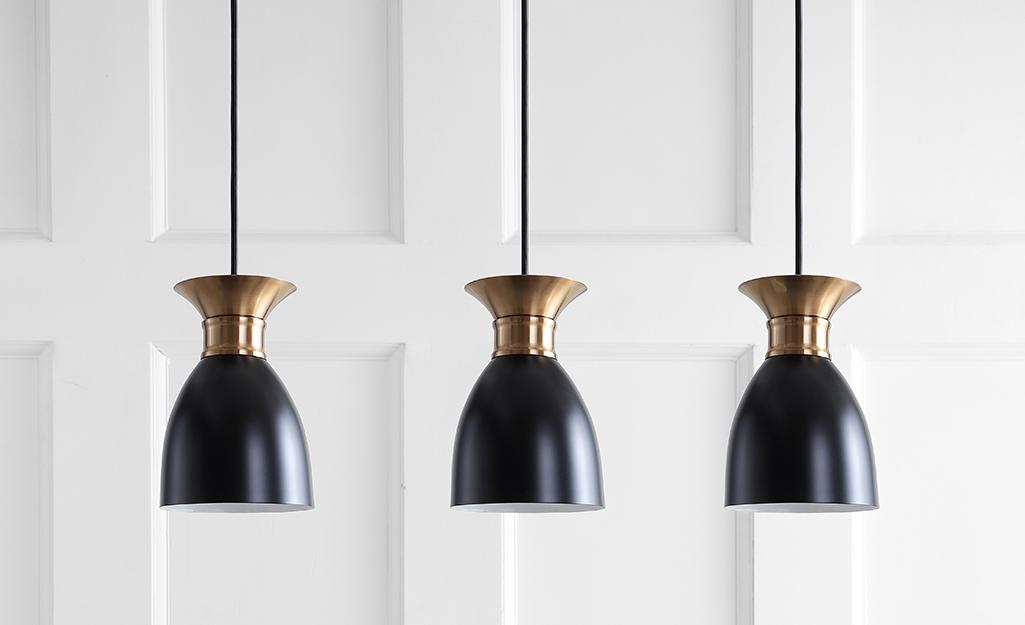 Three black and brass minimalist pendant lights.