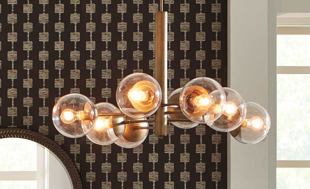 A modern chandelier with glass globes surrounding the bulbs.