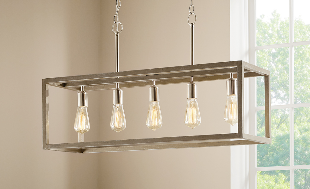 A rustic chandelier with a wood rectangular cage and exposed Edison bulbs.