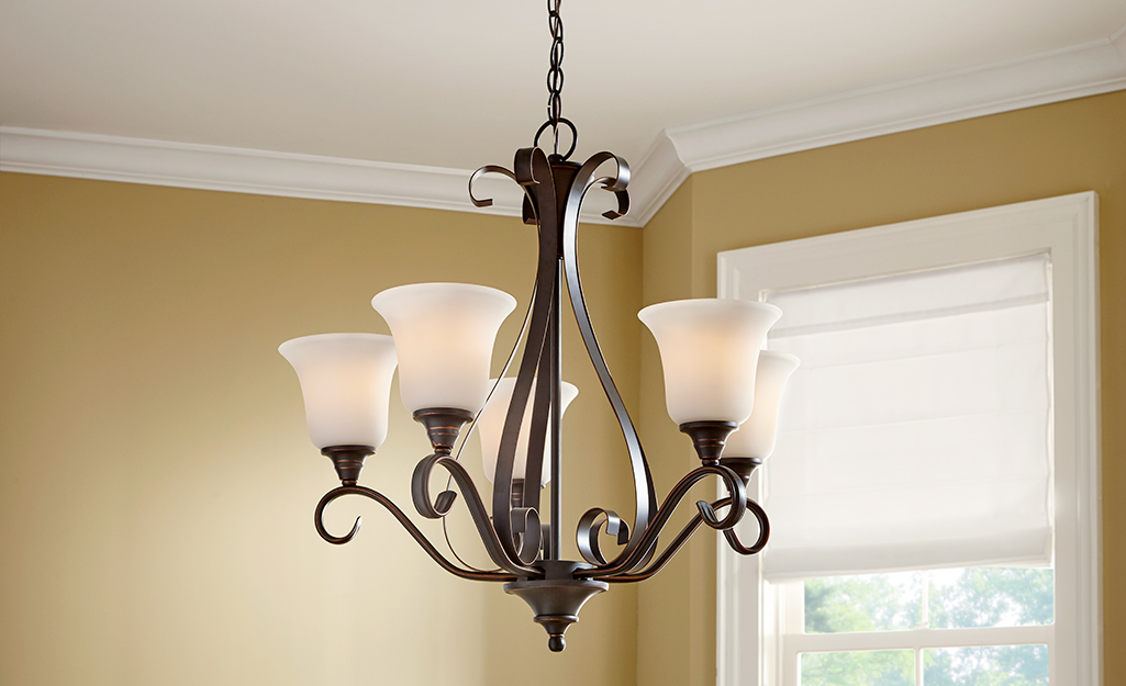 A classic chandelier with upward lights and bronze metalwork.