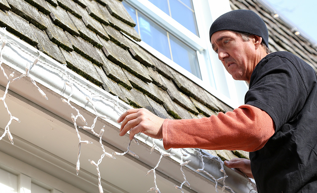 Installing Christmas lights for holiday decorating at your home.