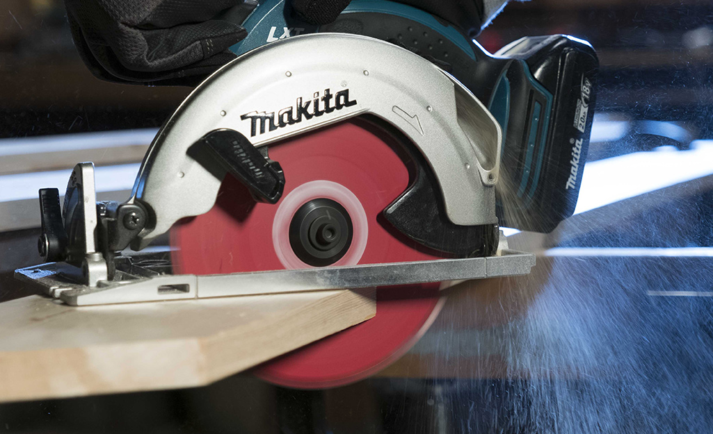 A circular saw cutting into a piece of wood.