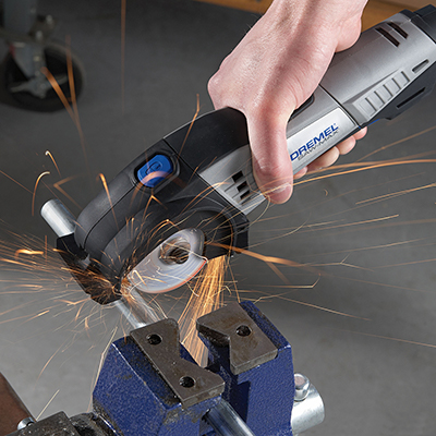 A person using a small, handheld circular saw.