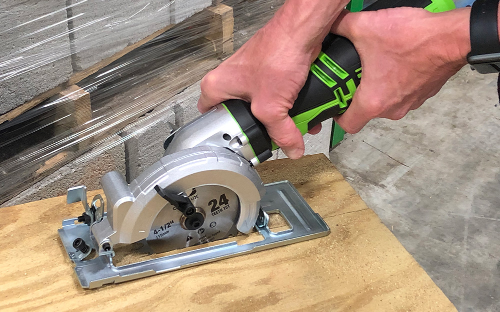 Someone using a circular saw to cut plyboard.