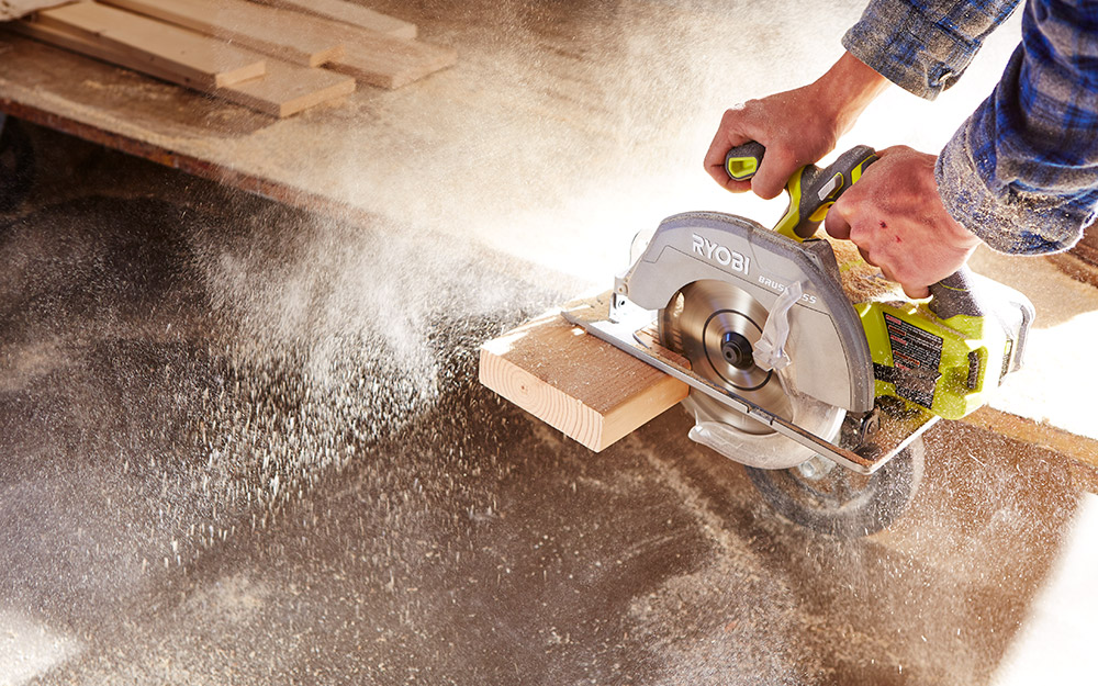 Man sawing a board with a circular saw.