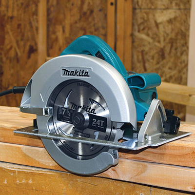 A circular saw sits on a stack of wood.
