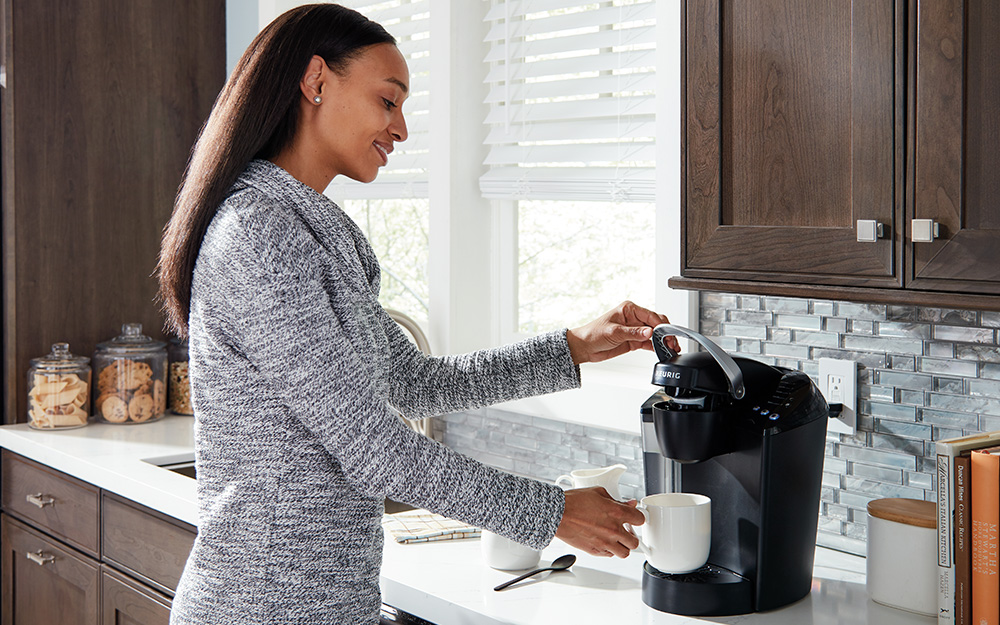 Woman making a cup of coffee from a single serve coffee maker.