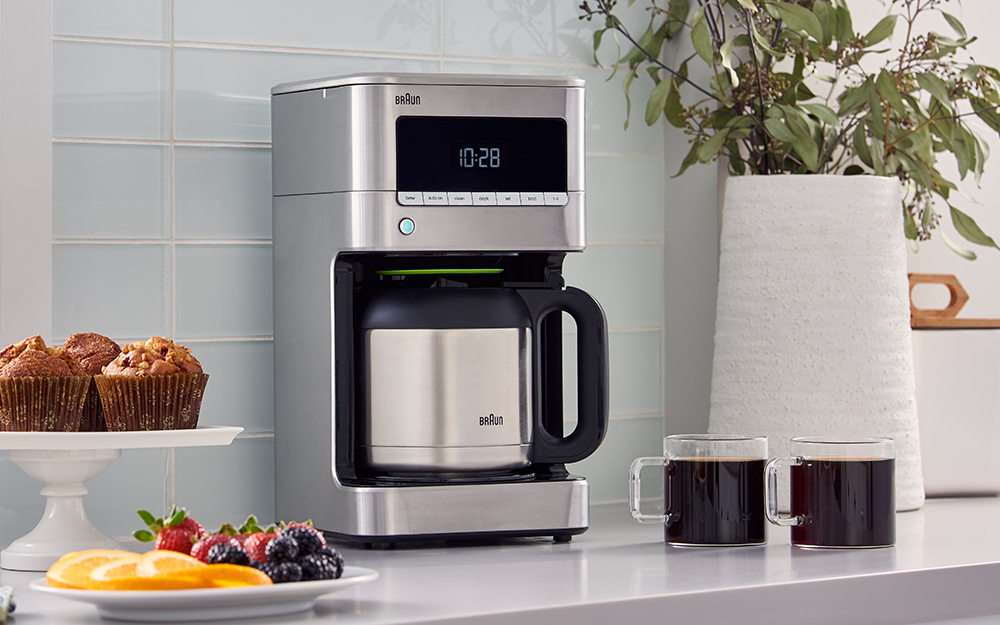An automatic coffee maker beside two cups of coffee and plates of fruit and muffins