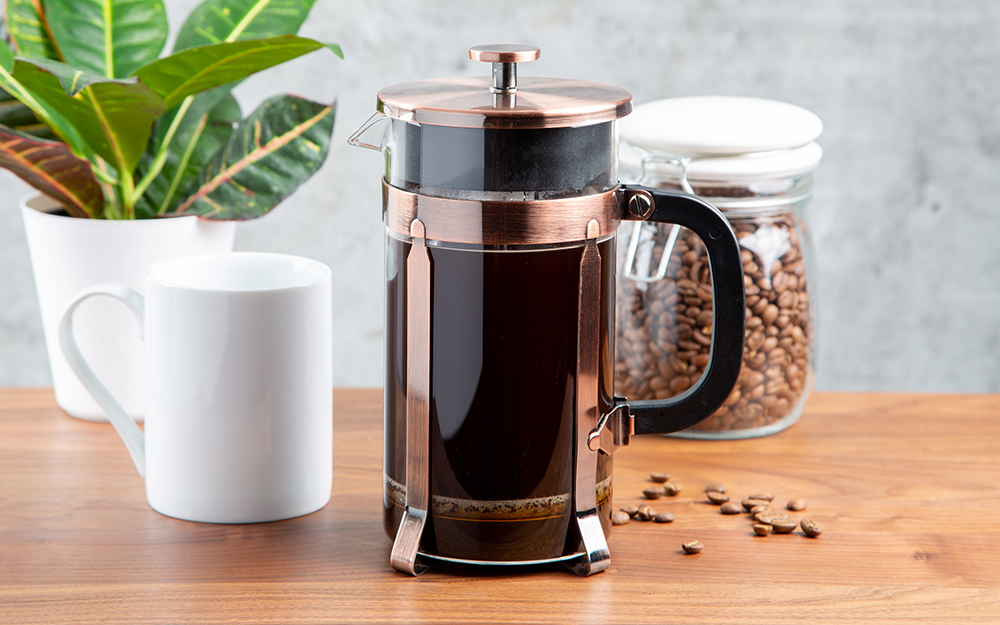 A French press coffee maker beside a mug and a jar of coffee beans.