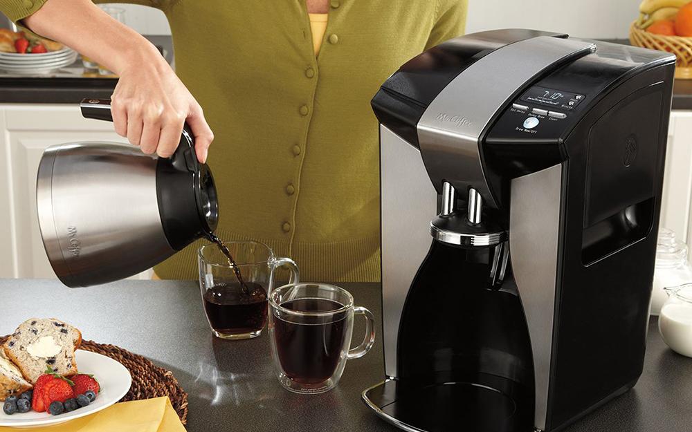 người phụ nữ rót cà phê vào cốc cà phê thủy tinh