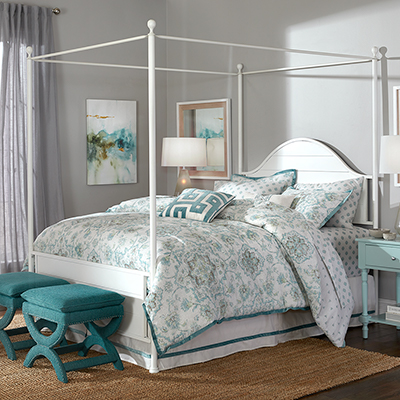 Green print comforter on a four poster bed