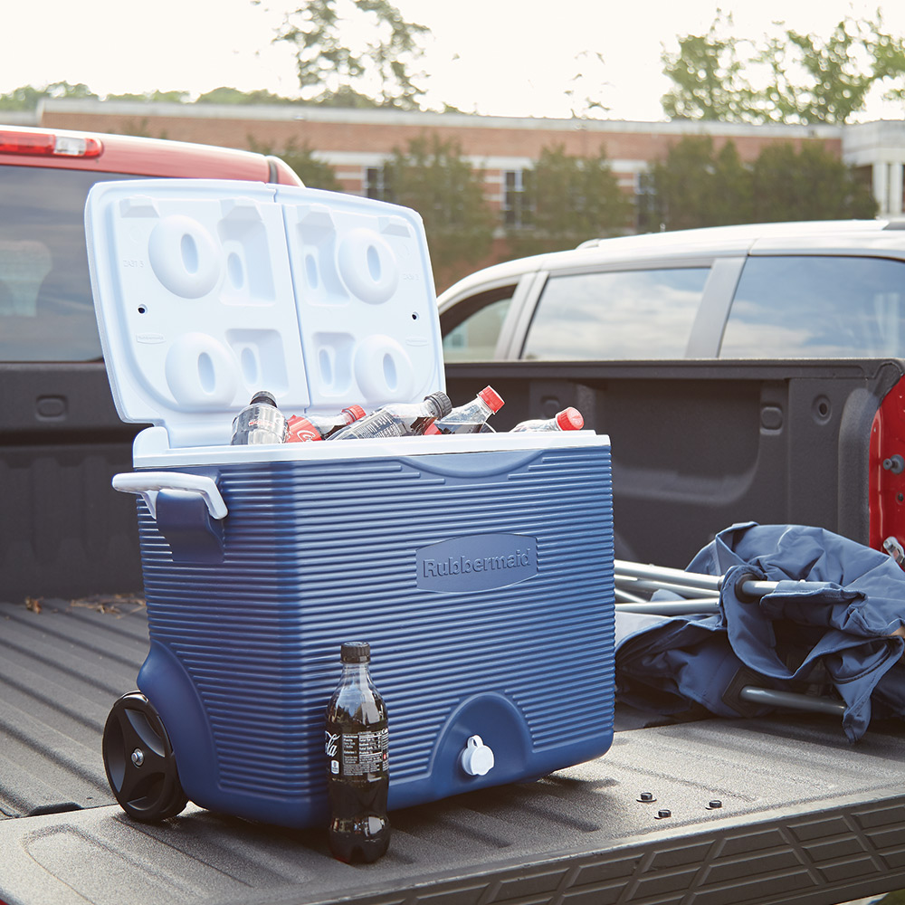 Cooler filled with ice and drinks sitting on tailgate of a pickup truck