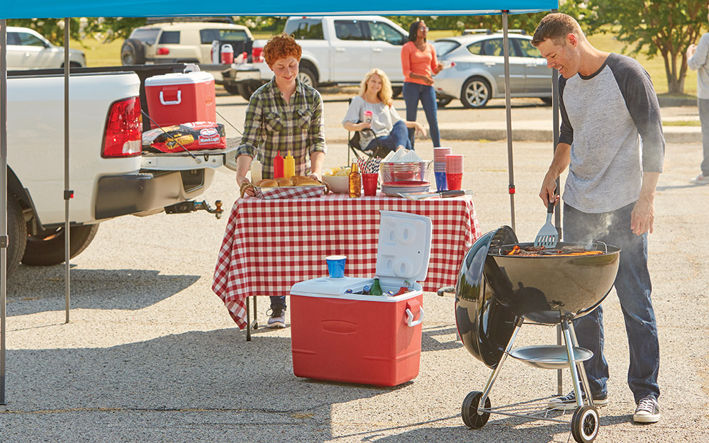 Red cooler and black barbecue grill being used by a man at a tailgate