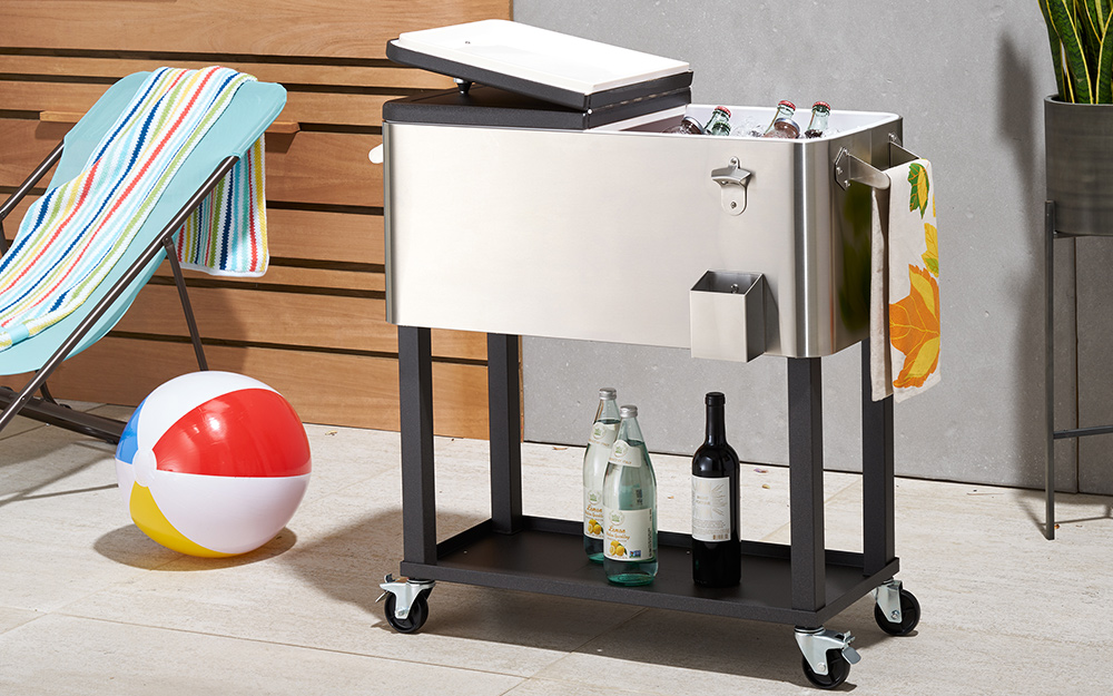 A stainless steel wheeled patio cooler with storage shelf