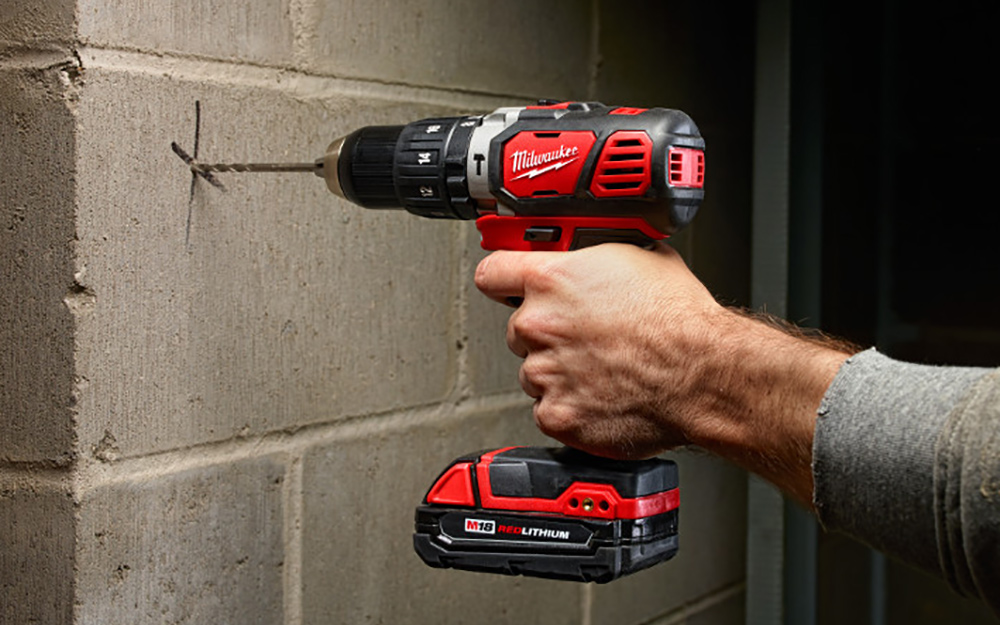 A cordless hammer drill is used to bore into a concrete block.