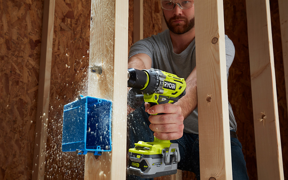 A cordless drill fitted with a spade bit bores through a piece of lumber.