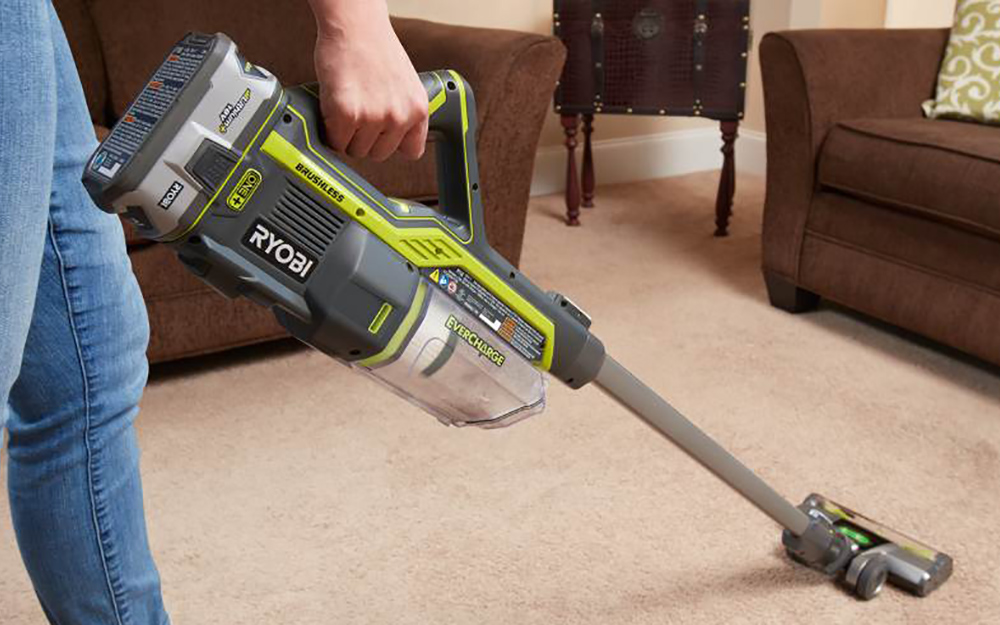 A person pushing a cordless vacuum on carpet