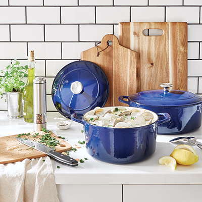 Wood cutting boards on a counter with blue cookware.