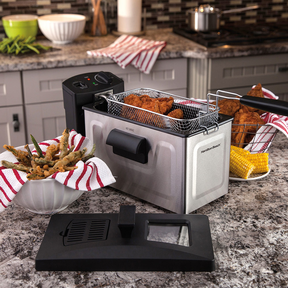 A countertop deep fryer being used to fry chicken and French fries.